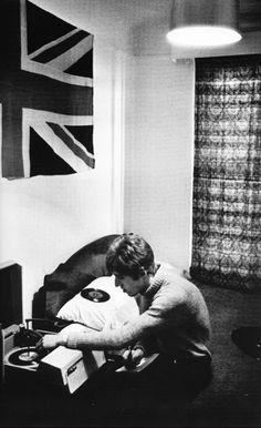 1965 Roger Daltrey playing records in his apartment.