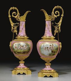 A PAIR OF ORMOLU-MOUNTED SEVRES STYLE PINK-GROUND EWERS <br />LATE 19TH/20TH CENTURY <br />Each of baluster form with an upright scroll handle, the spout cast with acanthus, the shoulder with stiff-leaf tips, painted front and back with putti either swimming and fishing or hunting and dancing within a chased oval surround, on a conforming socle and canted square base<br />16 in. (40.6 cm.) high (2)<br />