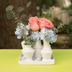 Our stylish grouping of ceramic bud vases is glazed in place on a square tray, creating exceptional stability for your table centerpieces.