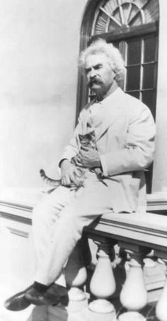 "Mark Twain with his cat ""Huckleberry"""