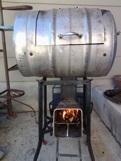 Beer keg turn into BBQ with a hole in the bottom through which the bbq slips over the rocket stove.