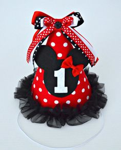 A super cute Minnie Mouse inspired 1st Birthday Party Hat for your Little Miss, perfect for a birthday party or cake smash photo shoot. You can also choose a different Birthday number for the front of the hat too!    *** This item is made to order, please allow 14 days plus postage time for your Party Hat to be created ***    The hat is handmade from cardstock covered in red polka dot fabric, soft black tulle trim and coordinating ribbon bows on top in shades of red, black and white. The hat…