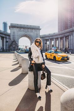 Jessica Wang wears a faux fur stole with faux leather pants and white booties for winter. Visit Notjessfashion.com for more winter outfit ideas, edgy winter outfits, leather pants outfits for women, and cozy winter looks. #winterfashion #womensfashion #outfitinspo
