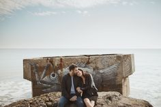 Couple sat on the beach, by the sea, next to a graffiti covered shelter in Yorkshire, UK.