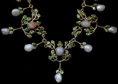 JESSIE M. KING (1875-1949) LIBERTY & Co. A gold necklace set opals and small peridots surrounded by green enamelled leaves. Each panel having a pearl drop.