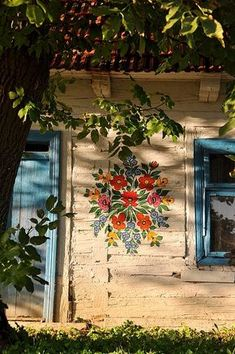 Cottage Charm - flowers on wall, blue door and windowframe
