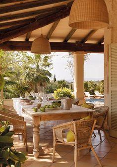 Comedor bajo un porche con sillas de mimbre