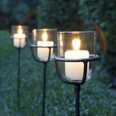 Steel and glass candleholders stake claim on romantic outdoor lighting with a sleek, modern look. Cup-shaped glass holder is cradled in simple metal base set on a tall, slender stake. Inserts into the ground wherever flickering light is welcome.