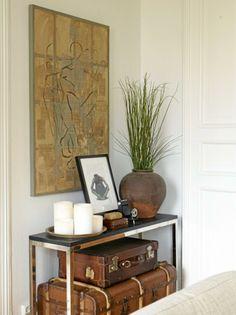 Gamle kofferter skjuler ekstra puter og andre ting som ikke skal stå fremme. Bildet er malt av beboeren selv. Bordet og keramikkurnen er fra Konzept HP.