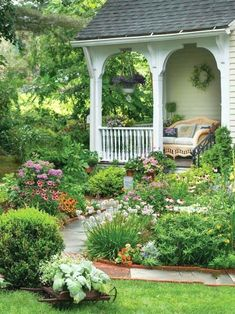 love the porch railing and plant filled curved bed leading to it