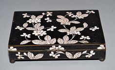 antique Chinese enamel hinged lid cloisonne box, raised on four ball feet, Black ground with wire cloud pattern and White flowering branch decoration