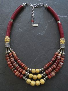 A necklace using my favourite combination of maroon and yellow colours which reminds me so much of Tibetan culture, bringing a quiet, calm and pleasing energy.  In the mix is lots of fabulous antique Carnelian with one or two antique quartz beads from Mali that surround nine yellow fancy Venetian wound African trade beads.  Two large Yemeni silver beads, two large antique Venetian beads from late 1800s early 1900s African trade. Lots of African maroon Vulcanite, brass spacer beads from a…