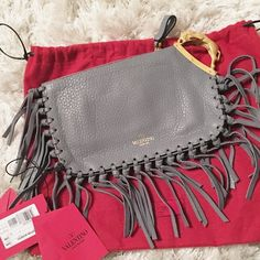 """Valentino Gray Scarab Fringe Leather Clutch Authentic Valentino Scarab gray leather clutch with fringe detailing and gold tone scarab handle. Simply amazing. Almost impossible to find in this color combination. Comes with dustbag and tags but is in good pre owned condition. Minor wear at hardware as photoed and normal signs of use.  Measures approx 8.5"""" x 5"""". Valentino Bags Clutches & Wristlets"""