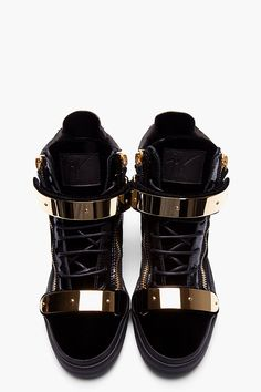 GIUSEPPE ZANOTTI - Black Velvet Gold-Bar Sneakers High top velvet sneakers in black. Round toe. Gold tone hardware. Black lace up closure with black patent leather eyerow. Leather logo patch at tongue. Foldover velcro straps at shoe face with metal bar embellishments. Signature zip closures at eyerow and heel collar. Leather pull tab in metallic gold. Contrast matte leather and patent leather paneling throughout. Black rubber foxing. Tone on tone stitching. Made in Italy. $1050 CAD