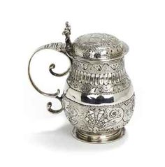 A Dutch silver mustard-pot  Mark of Claes Muntinck, Groningen, 1692/93  Of baluster shape, on circular foot, the body chased with flowers, leaves, shells and cannellures against a granulated ground, with S-shaped handle, the lid chased with two shields against a granulated ground, marked on base  9.6 cm. high  126 gr.