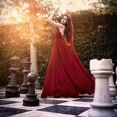 The chessboard indicates to me that the woman feels like a pawn...or is she a queen?  Notice she is in between the black side and the white side.  Is she evil or good?  Is she indecisive about which side to choose?