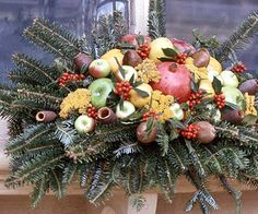 A dried pomegranate is the vibrant focal point for this windowsill box. Nuts and pods provide muted colors that offset golden yarrow, apples, lemons, and red-orange berries. All are nestled in a base of fir sprigs.