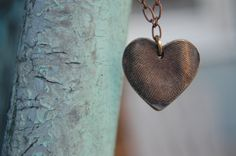 "This style of symmetrical heart is perfect for adult-sized prints and makes a special keepsake gift. As a larger heart, this pendant measures approximately 3/4"" across at its fullest point by 3/4"" in length.  To create this necklace, a fingerprint impression is cast in bronze and hand-cut in a symmetrical heart. After firing, the entire pendant is oxidized (or darkened), hand polished, and tumbled to create a beautiful patina that highlights all of the unique ridges and valleys of your loved…"