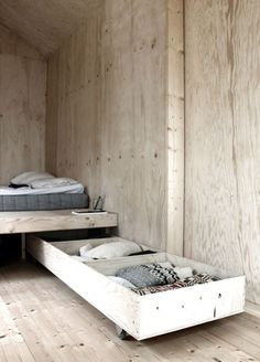 I like how the beds are at right angles so no one gets stepped on when the back bed person gets out of bed.   Spinning wheels on foot of trundle and a pole pinning it underneath the larger bed it can swing out on. Like a jack knife blade motion.