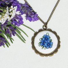 Blue Floral Vintage Style Hand Embroidered Necklace This pendant features a mix of blue flowers. The flowers were delicately hand embroidered using cross stitching techniques. The design was set into a bronze tone pendant frame and hangs from a matching bronze tone chain. Pendant