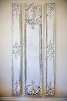 Boiserie panels painted in a creamy white with a cool blue and a touch of gold washed over the surface makes them look so much more authentic. ~ Summer Decorating Ideas