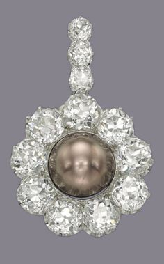 GILLOT & CO. - A VICTORIAN COLOURED NATURAL PEARL AND DIAMOND PENDANT, CIRCA 1900. Set with a brown button-shaped natural pearl, measuring approximately 15.50 - 15.75 x 11.80 mm, to the old-cut diamond surround and pendant loop, 5.3 cm, mounted in platinum and gold, signed Gillot & Co.