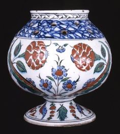 Iznik c.1560-80 Vase + lid. Made of polychrome underglaze pottery. The body is of globular form with a perforated shoulder, short concave neck and everted lip, standing on a flared pedestal foot which appears to be solid.  It is painted in cobalt-blue, black, viridian green and bole-red with curved feathery leaves and rose stems between cypress trees, prunus and small clasped floral bouquets.  The pierced shoulder is painted with blue marbling below a cable band.  162mm high.
