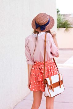The hat with a blue bow adds a nice touch to the peach polka dot skirt.