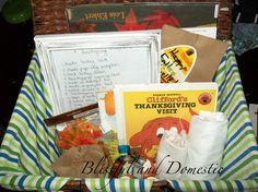 A Thanksgiving themed basket for kids with instructions and items to make Turkey shirts, paper bag pumpkins, and a thankful tree along with books from the local library.
