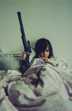 """""""Nooma Sick In Bed Listening To Her Parents Fight"""" Laura Honse, Hamburg Germany, 2005. Honse said """"when I came to visit, Nooma was sick in bed. Her parents were having stress in their relationship and she was listening to them fight in the hallway. The toy gun was lying next to her on the bed."""""""