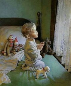 A young boy praying while he looks through his window towards the sunlight.