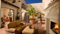 Mediterranean Patio with Spanish tile roof, Outdoor wicker furniture, Arched doorway, Musa Basjoo Banana Trees, French doors