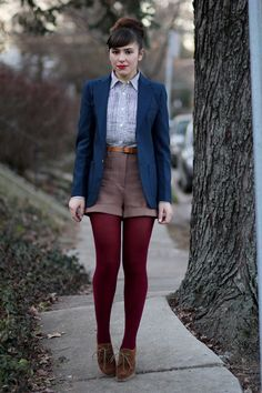 high waisted shorts and dark rouge tights against a lighter and darker shade of blue. fly outfit.