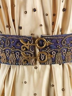 * Belt of the evening dress  fall 1939 silk, glass, rhinestones, metal Elsa Schiaparelli  the belt, featuring glyphs of Jupiter and Mars, is the more obvious reference, but the embroidery, all applied by hand, could symbolize shimmering stardust or astrological symbology. In planetary mythology, Mars, the god of war, is the rebellious son of Jupiter and Juno. Jupiter, or Zeus, was worshipped as the king of gods in ancient Greece