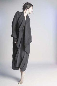 Atelier Marie Labarelle Manteau Sensei Papillon en lin noir,  porté sur une jupe méharée en tissu de costume masculin noir à rayures blanches.