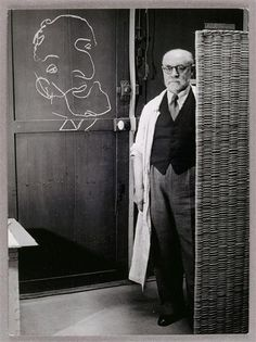 Brassaï: Henri Matisse standing against a screen and drawing with chalk, 1939