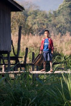 Inle Lake Boy - A village boy watches from his stilt house near Kaung Daing on the north shore of Inle Lake in Burma.