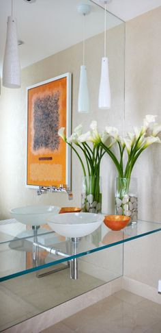 Light and airy glass bathroom counter with vessel sink and a touch of fresh flowers to add to the decor.