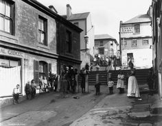 Large group of people, including children, in laneway in Sydney's Rocks area with terraces, shops, hotels and steps and the Cheap Cash Grocer on the wall of Susannah Place in the background.