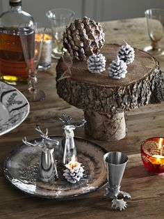 This woodland Christmas decor consists of deer and moose shot glasses, frosted pinecone candles, and a wooden cake stand. #christmas #decorations