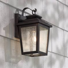 "Compact and stylish, this outdoor wall light was inspired by carriage house designs and comes in a handsome Chelsea bronze finish. 12"" high x 6 1/2"" wide. Extends 7 1/2"" from the wall. Uses one maximum 60 watt standard-medium base bulb (not included). Style # 2N105 at Lamps Plus."