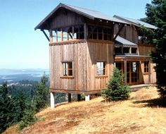 Mount Dallas Cabin, San Juan Island By David Vandervort Architects.  600 square feet. Steel rebar was drilled into the rock, providing reinforcement for sonotube concrete piers, which support the structure. Reconditioned heavy timber beams were used in a post and beam construction method. Two ladder/stairs serve flanking window-lined loft bedrooms on the upper floor level. The cabin also integrated photovoltaic energy for light and heat.