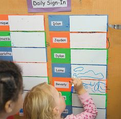 a girl scribbles near her name on a Daily Sign-In poster