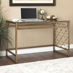 Scratch and mark resistant brushed goldtone powder coating finishes this quatrefoil style writing desk. This transitional desk is coupled with a tempered glass top.
