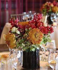 Texture and color are essential when creating a unique Thanksgiving centerpiece. This arrangement features a lush mixture of rich colors and blooms, including red Mokara orchids, red Cymbidium orchids, amber Football mums, green 'antique' hydrangea, and red-orange bi-color roses. Take a few fresh berries before you start on your pies and cut some branch accents from your garden to spruce up your centerpiece.