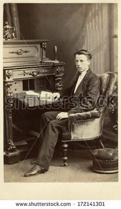 CIRCA 1868 A vintage Cartes de visite photo of a young gentleman. The man is sitting in front of a desk with a book. A photo from the Victorian era. You can purchase a digital copy of this photo at the above web link.