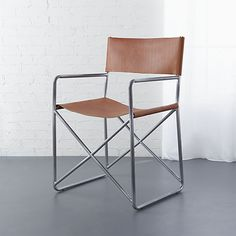 An ode to the iconic director's chair, soft leather takes a seat on slim iron frame with x-shaped base. Pull up to dining table or let it solo as accent chair.