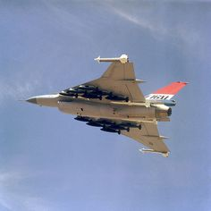 An air to air left underside view of an F-16XL aircraft. The aircraft is armed with two wing tip mounted AIM-9 Sidewinder and four fuselage mounted AIM-7 Sparrow missiles along with 12 500-pound bombs. Date