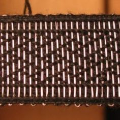 Silver brocaded band. This is the Birka strapwork motif that is often done as a threaded-in weave based on Carolyn Priest-Dorman's adaptation
