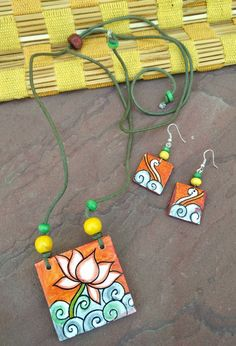 Divine Lotus Mural Handpainted Necklace with Earrings at CraftsandLooms. Handcrafted Mural Necklaces, Mural Earrings, Mural Studs and more. Wide variety of Mural art necklaces at lowest prices Terracotta Jewellery Making, Terracotta Jewellery Designs, Thread Jewellery, Fabric Jewelry, Teracotta Jewellery, Mandala Jewelry, Handmade Earings, Art Necklaces, Craft Ideas